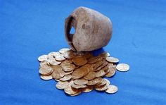 Gold coins and the ceramic jug in which they were found hidden are displayed at the Arsuf cliff-top coastal ruins, 15 km (9 miles) from Tel Aviv, July 9, 2012. The 1,000-year-old hoard of gold coins has been unearthed at the famous Crusader battleground where Christian and Muslim forces once fought for control of the Holy Land, Israeli archaeologists said on July 11, 2012