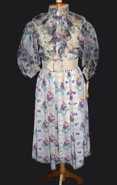 """A two-piece ensemble worn by Shirley MacLaine as she portrayed """"Aurora Greenway"""" in the Oscar winning classic Terms of Endearment (1983). Made of a floral-print silk, the blouse has puffy sleeves and a ruffled collar while the matching skirt is knee length and pleated"""