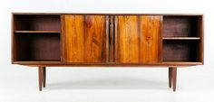 Axel Christiansen Danish modern credenza, rosewood, design attributed to Gunni Omann, circa 1950s, four sliding doors with sculpted handles and three drawers in center, raised on four round tapered legs, signed with applied foil label to interior.