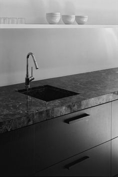 Black wood cabinets + dark grey natural stone countertop. Kitchen interior by Hans Verstuyft.