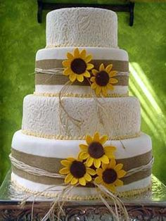 Four tier white and straw country wedding cake decorated with handcrafted yellow sunflowers  add some red bandana in there