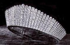 """Kokoshnik+Tiara_Queen+Elisabeth. Al igual que los imponentes broches devant de corsage se sujetaban gracias al corsé, las grandes tiaras quedaban fijadas mediante los recogidos con moño alto. A partir de 1907, la influencia rusa tuvo su impacto en las tiaras kokoshnik (en ruso """"cresta de gallo""""), inspiradas en un tocado femenino tradicional. Para conferir cierta levedad al aspecto macizo que puede tener el kokoshnik, Cartier creó varias piezas con diamantes suspendidos en la montura."""