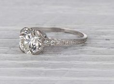 Vintage Art Deco engagement ring made in platinum and centered with a GIA certified 2.33 caratold European cut diamond with Kcolor and VS1 clarity. Circa 1920 ElegantArt Deco setting that emphasizes the beautiful old European cut diamond. Old European cut diamonds feature thicker and more interesting facets that newer stones often lack. The cut was the prevailing style from the 1890s to the 1930s. Learn more about Art Deco era engagement rings. Diamond and gold mining has caused…