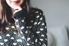 Foto aconchegante com clima de outono inverno. Mulher usando suéter de tricô preto com corações cor de creme e bolinhas.