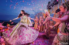 Bridal entry ideas | Bride showered with flowers | Pink and pale yellow lehengas | Bride Twirling | Curated By Witty Vows