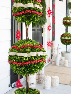 Rather than using Christmas trees, this front entrance is flanked by a pair of lush boxwood topiaries which lay the foundation for the green, red and white color scheme.