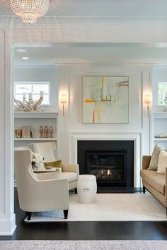 Chic living room features a gray and orange abstract art piece illuminated by Dauphine Sconces ... #wallsconceslivingroom