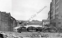 "Caption ""Canal basin with moored barges"" (Looks like a image taken from W. Boyers at Irongate Wharf, Paddington Basin)."