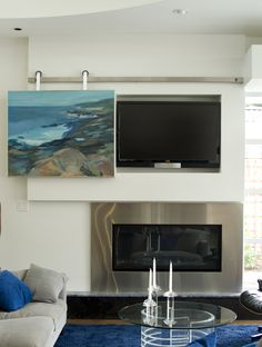 Cover your television with art! Premium stainless steel modern sliding door hardware, ready to carry whatever you hang from it, at krownlab.com. #architecture #interiordesign