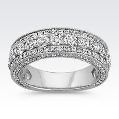 One hundred and sixty-five round diamonds, at approximately 2.25 carat total weight, immensely radiate in this breathtaking wedding band. Each diamond has been hand-matched for consistent fire and color and is pavé-set in quality 14 karat white gold. The regal design is complete with milgrain detailing both on the top and on the sides of the ring.
