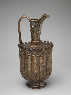 Ewer Date: ca. 1180–1210 Geography: Iran, Khurasan Culture: Islamic Medium: Brass; raised, repoussé, inlaid with silver and black compound Dimensions: H. 15 3/4 in. (40 cm) Diam 7 1/2 in. (19.1 cm) Classification: Metal