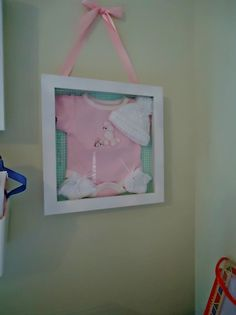 Wall hanging. I used a shadow box to and one of the girls first onesies, hat and booties as decor.