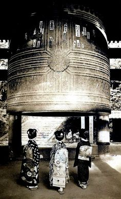 Two Maiko girls and a Geisha standing underneath the Great Bell at the Chion-in Temple in Kyoto 1930s