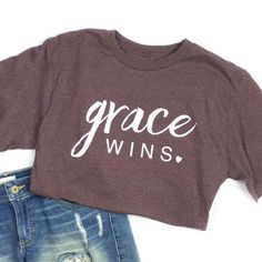 "NOTE: This item for some sizes takes days to process before shipping out. On a plum blended unisex tee with our ""Grace Wins"" design. FIT: Unisex - Runs true to size. *Plum with vintage white desig Christian Clothing, Christian Shirts, Tween Fashion, Womens Fashion, Fashion Top, Fashion Forms, Skull Fashion, Fashion Trends, Fashion Black"