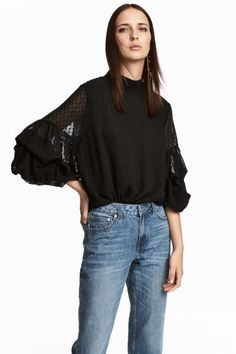 Wide, double-layered blouse in a plumeti weave with a stand-up collar and covered buttons down the back. Long flounced sleeves with elasticated cuffs, and a