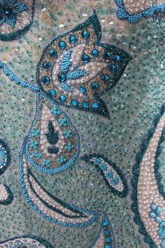 Ramon Valera sequined and beaded gown or `Terno', Philippines, 1960s, the iridescent sequined ground adorned to the hem with blue and white sequins and beads in swirling Paisley motifs, with babarahin stiffened `butterfly' sleeves and gauze over-panel edged in blue beads and droplets, rosettes to the shoulders