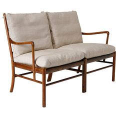 Two-seater sofa in rosewood and cane with cushions in cream colored textile. Designed by Ole Wanscher in 1949. Made by P. Jeppesen, Denmark