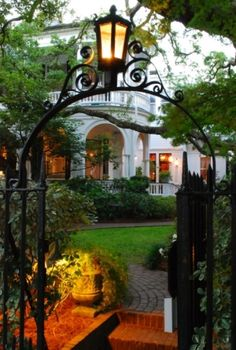 Iron gate with lantern, brick walk leading into beautiful Charleston, SC garden.