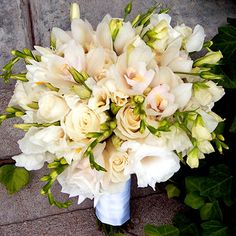 Sparkling white roses and orchids are classic choices for wedding bouquets. Here, the two favored flowers combine to form a fragrant, dome-shape bouquet.