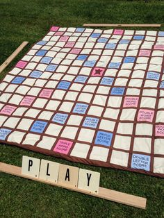Lawn Scrabble quilt. Not bad for my first try.  Made from Bella Solids 30's colors, 2.5 yds. brown fabric, 6 yds of fabric for the back, a king size sheet of low loft batting, iron-on printable paper and time. Tiles are house number/letter stickers on 100 5x5 precut blocks.