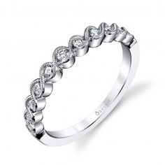 This romantic vintage style wedding band features a total weight of 0.20 carats of dazzling round brilliant diamonds in channel settings with two rows of milgrain beaded ribbons of white gold metal swirling around each diamond and crossing over and under each other.  As a wedding band, this ring will truly enhance any bridal set, and when used in a stackable fashion set, it will create a graceful addition to your collection.