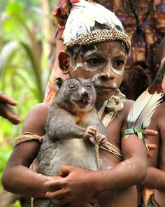 "The boy is holding a ""Silky Cuscus"" as a pet, possibly, in  Papua, New Guinea."