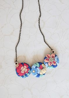 "Flora Lexington Indie Necklace 27.99 at shopruche.com. This charming antiqued brass necklace holds a pendant handcrafted from lightweight laser cut bamboo and whimsical blue fabric buttons with a colorful floral print.16"" long, Pendant: 2.75"" long"