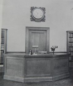 The original front desk in 1916 was positioned in the main reading room underneath the Alice D. Curtis clock and the between the book stacks that are still with us today.