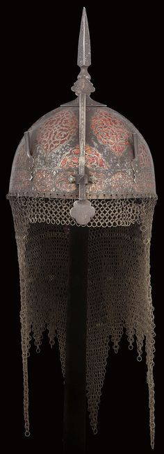 Persian kulah khud helmet, mid 19th century,  domed skull chiselled with a series of large cartouches filled with arabesque interlace, similar small cartouches between, a band of cartouches encircling the base, alternately filled with flowers and pious invocations, all picked-out in koftgari (rubbed), all in low relief on a transluscent red enamel ground, and fitted with sliding nasal, plume-holders, spike and camail of iron and brass butted mail, 11in (28cm).