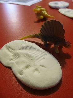 Dinosaur fossil making @ Teach Through Play For a great christmas preset add a fewplastic dinossaurs to some home made white playdough! #toddler #dinosaur