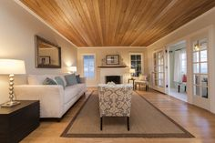This contemporary living room has wood floors and ceilings. A neutral rug helps warm up the room.