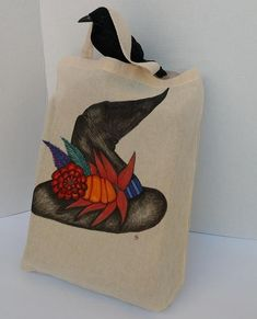 This magical bag is sure to be a treat. Your little goblin will love trunk or treating with this canvas tote! This lightweight cotton canvas bag is hand painted and features a witch's hat that has been beautifully adorned with Autumn flowers,feathers, and a small pumpkin. Colors on design include Halloween Gift Baskets, Halloween Candy Bags, Halloween Gifts, Halloween Ideas, Vintage Baptism, Library Bag, Magic Hat, Fall Bags, Trick Or Treat Bags