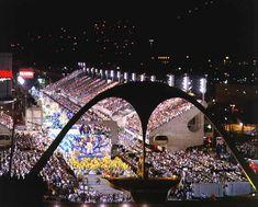"""Passarela do Samba, 1983, Rio de Janeiro  Oficialmente chamada Passarela Professor Darcy Ribeiro e popularmente conhecido como Sambódromo, o centro do carnaval carioca localiza-se na avenida Marquês de Sapucaí, Rio de Janeiro, e nasceu com a missão de """"dar ao povo o samba"""". Na parte final da passarela, as arquibancadas se separam para abrir espaço à monumental Praça da Apoteose, assinalada por um grande arco. Ali está também o Museu do Samba."""
