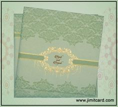 A Glamorous Metallic Fabric Marriage Invitation in Green Color with Central oval Motif surrounded by elegantly designed twines in gold adds charm.