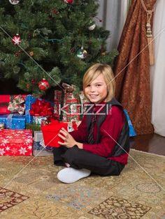portrait of a boy with his gift box. - Portrait of a boy with his gift box sitting next to christmas tree, Model: Josh Chapman