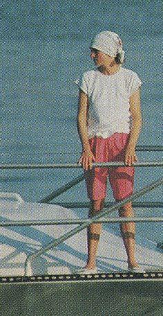 Diana. Long shorts, white tee & head wrap.