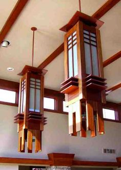 The chandeliers hang in the dining end of the great room in front of a wall of windows. - CLICK TO ENLARGE