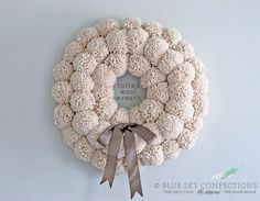 Large tufted pom pom wreath. Love the 3-deep design. Done using a wool-acrylic blend yarn & a large pom pom maker. The pom poms were then tied into place on a foam wreath form.