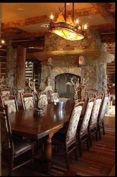 fabulous dining room in this log home. The triple tee pee light fixture with rawhide surround, rustic fireplace, and antler candle sticks are so rustic and pretty