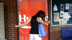 Huge me do: A female student squeezes the Coca-Cola vending machine at the National University of Singapore