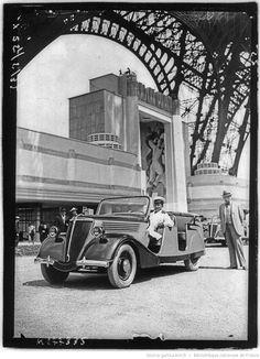 [Exposition internationale des arts et techniques, Paris 1937 : sous la Tour Eiffel, une automobile stationne devant le pavillon du Cinéma de la Photographie et du Phonographe (25 mai 1937)] : [photographie de presse]