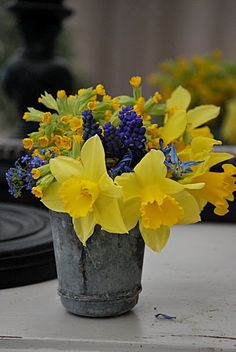 A SMALL BOUQUET OF YELLOW & BLUE FLOWERS IN A PETITE ANTIQUE CONTAINER.