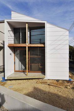 写真提供:D.I.G Architects 吉村真基+吉村昭範 / D.I.G Architectsが設計した、愛知・名古屋の住宅「丘のふもとの十字架構」です。 ささやかな住宅の計画です。 敷地は公園にむかって開けた角地で、そこにまず柱を一本立て、居住環境を構成するよりどころとしてその柱を基点とした座標軸を想定しました。 この軸は住宅の内部においては空間を緩やかに分節する単純なXYZの架構として現れます。 座標軸を想定した上で、次に住宅の外皮としてのボリュームを設定しています。 1階は架構とは切り離したBOXの中に収納や水回り等のユーティリティを納め、あとは生活のメイン空間として十字の架構の下でなんとなく領域を分けながらも広々と使います。2階は「座標軸」に乗る形で2つの床を設けています。住宅としてはそれだけです。 2階の床は軸にそって外に伸びています。一方はバルコニー、一方はアプローチの庇という形で役割を与えられていますが、その機能的な側面と共にここでは架構が建築の外皮を破って外にのびていくという振る舞いが重要です。 この架構は住宅を構造的に成立させるためのものですが、...