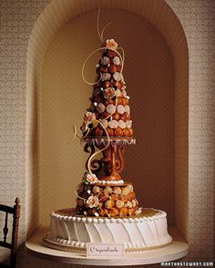 """This towering confection is the traditional wedding cake of France. The name croquembouche, which means """"crunch in the mouth,"""" refers to the hard caramel that coats delicate puffs of pate a choux filled with vanilla cream. The top tier rests on an edible nougatine base, made of caramel and crushed almonds. The roses and ribbons are pastillage, a sugar paste that dries with a porcelain-like finish; the giant swirls are pulled sugar."""