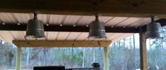 Metal buckets turned into light fixtures for a rustic outdoor bar area