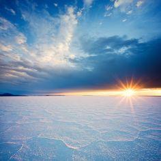A rising sun illuminates the crystalline salt patterns of Utah's Bonneville Salt Flats.