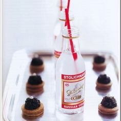 Mini bar bottles of Stoli and caviar on blinis.