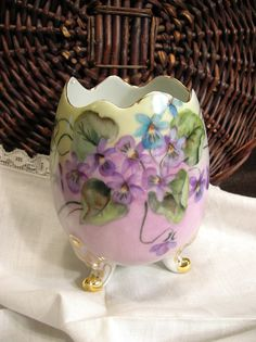 Vintage Bavarian footed china egg, hand-painted violets with gold gilt trim; the artists initials, E. W. and date, 59, are present. The egg is marked Plankenhammer Flass Bavaria Germany (1908 - c.1978). Beautiful hand-painted violets in shades of purple with green leaves on a background of lavender, cream, and dusty rose. Also, the three feet are accented with gilt, as is the top edge of the egg. The colors of the actual item are a bit more muted than my photos show.  Measurements: 5-1/2...