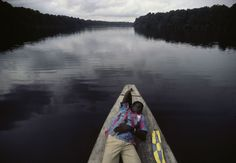 A young man rests on a boat cruising up the Ogooué River. Gabon. 1984. © Bruno Barbey / Magnum Photos