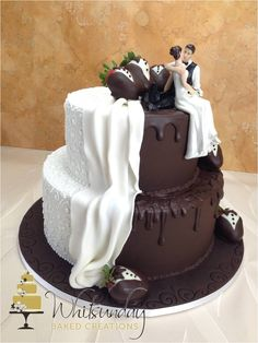 A two tier wedding cake half in chocolate and half in white fondant.  Chocolate dipped strawberries to complete.
